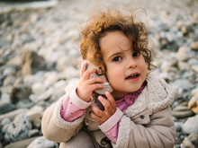 Portrait Of Little Girl Listening To Conch With Rapt On Stony Beach