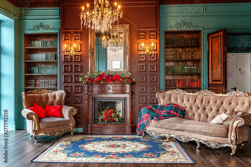 Obraz Luxury classic interior of home library. Sitting room with bookshelf, books, arm chair, sofa and fireplace. Clean and modern decoration with elegant furniture. Education read study wisdom concept - fototapety do salonu