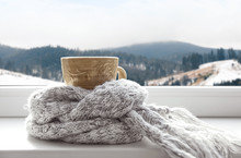 Hot Drink And Warm Scarf Near Window With View Of Winter Mountain Landscape