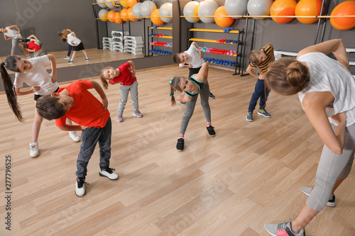 Poster Fitness Cute little children and trainer doing physical exercise in school gym. Healthy lifestyle