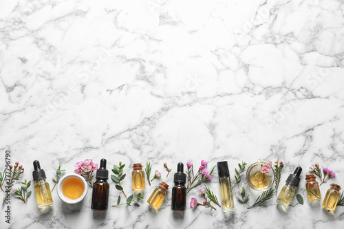 Fototapeta Flat lay composition with bottles of natural tea tree oil and space for text on white marble background obraz