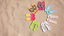 Flat Lay Composition With Flip Flops On Sand, Space For Text. Summer Beach Accessories