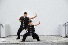 Father And Son Are Engaged In Wushu In The City. The Photo Illustrates A Healthy Lifestyle And Sport. The Father Trains The Son.
