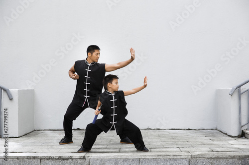 Father and son are engaged in Wushu in the city Canvas Print