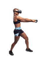 Athletic Woman Exercising While Playing Video Game By Practicing VR Sword Fighting Or Swordplay With A Virtual Reality Headset And Controller. Depicts Healthy Active Gaming For Fitness.