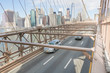 Cars traveling over the Brooklyn Bridge. City of Manhattan in the background. New York, USA.