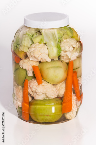 A jar full of large pickled green tomatoes, carrots, and cauliflower in a jar isolated on white.