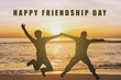 "Two Silhouette people jumping for joy on sunset beach with ""happy friendship day"" text"