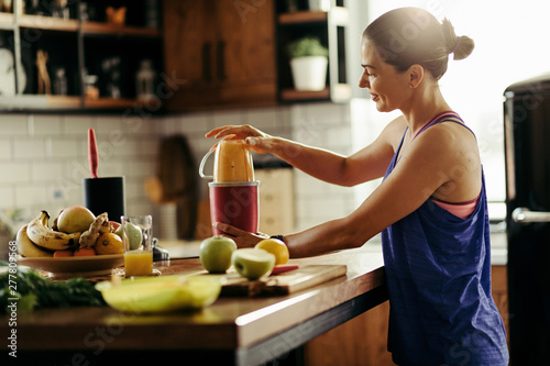 Fotografie, Obraz  Young sportswoman making healthy smoothie in the kitchen.