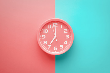 Top view red clock alarm clock not colored background divided vertically into red and green color