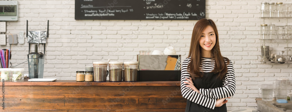 Fototapeta Young woman owner of a cafe stand in front of coffee counter, young entrepreneur conceptual, dimension image for banner