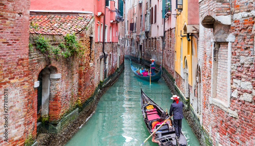 Canvas Prints Venice Venetian gondolier punting gondola through green canal waters of Venice Italy