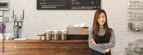Fototapeta Young woman owner of a cafe stand in front of coffee counter, young entrepreneur conceptual, dimension image for banner obraz