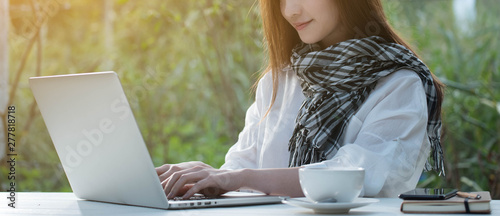 Obraz Beautiful young teenage woman freelance work with laptop with a cup of latte on sun light, freelance lifestyle conceptual - fototapety do salonu