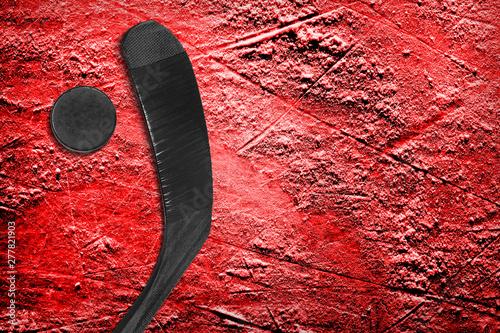 Fototapeta  Hockey stick and puck on red ice