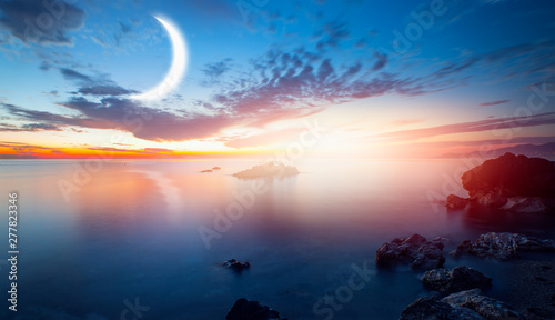 Crescent moon rising above calm sea in sunset sky Elements of this image furnis Wallpaper Mural