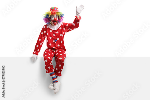 Foto Funny clown sitting on a white panel and waving