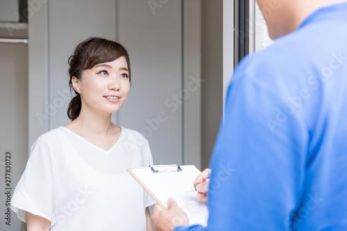 玄関でサインする女性 Fototapete