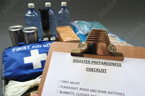 Cuadros en Lienzo Disaster preparedness checklist on a clipboard with disaster relief items in the background