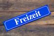Freizeit Schild blau auf Holz