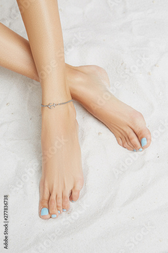 Cropped front shot of lady's legs with blue pedicure, wearing ankle bracelet with double chin, adorned with silver insertion in view of anchor Canvas Print