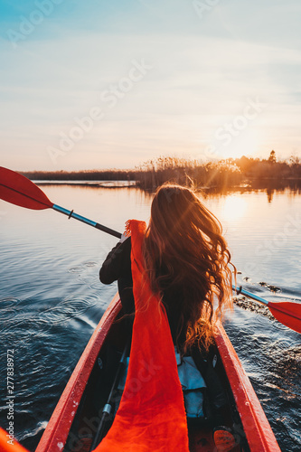 Fotomural  Back view of happy cute girl holding paddle in a kayak on the river