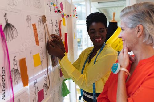 Fototapeta  Female fashion designers discussing over sketch design