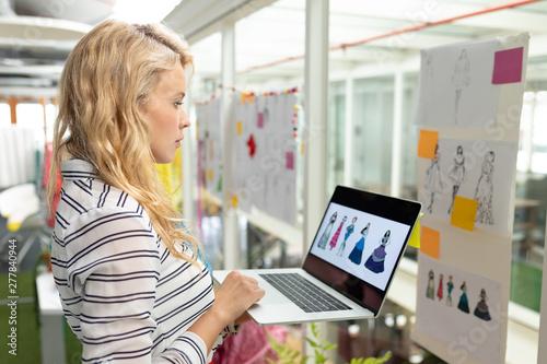 Fototapeta  Female graphic designer using laptop in design studio
