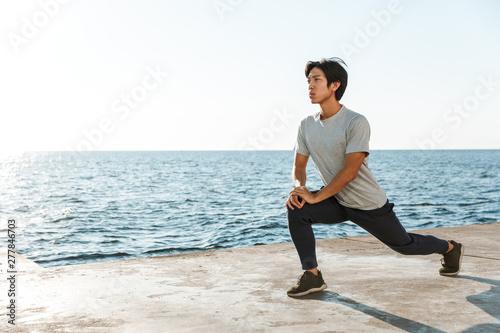 Fotografiet  Confident fit asian sportsman exercising outdoors