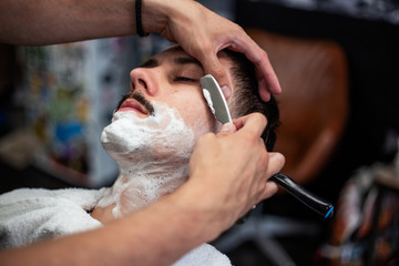 Razor in hands of specialist barber. Barber shaving a man in a barber shop, close-up. Man mith mustaches having a shave