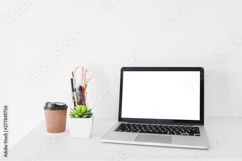 Valokuva  Laptop with blank white screen and disposal cup on desk