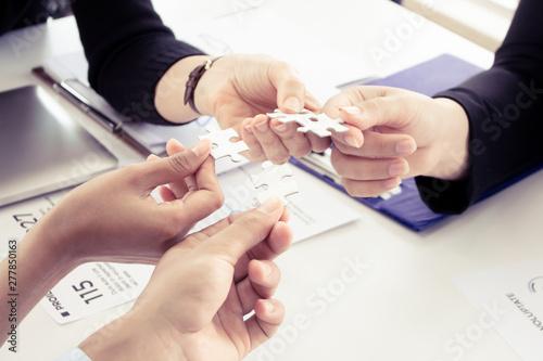 Fototapeta  Closeup of businesspeople holding jigsaw puzzle.