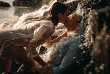A Couple During Lovemaking Next To A Waterfall.