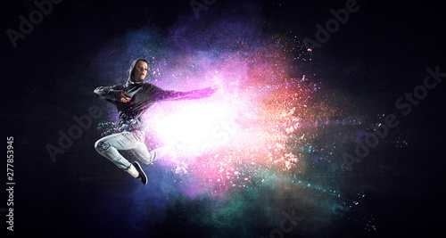 Spoed Foto op Canvas Dance School Modern female dancer jumping in hoodie with colourful splashes background. Mixed media