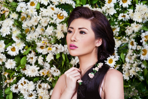 Photo Asian woman with daisies in hair on the flower background