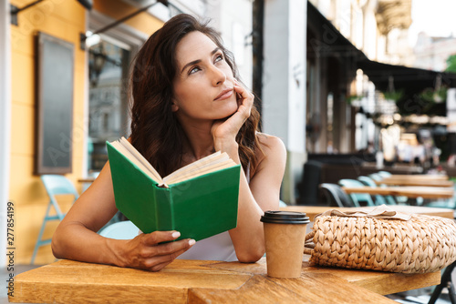Obraz na plátně  Portrait of brooding nice woman drinking coffee from paper cup and reading book