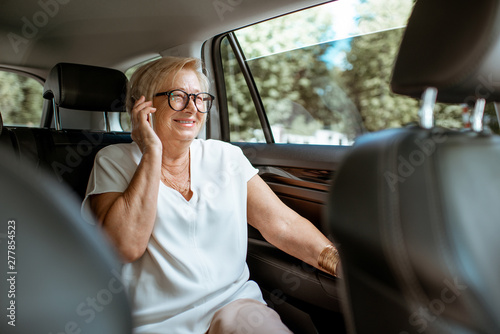 Senior business woman talking with phone while sitting on the back seat in the modern car Poster Mural XXL