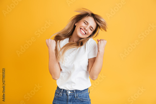 Obraz na płótnie Emotional young blonde woman posing isolated over yellow wall background dressed in white casual t-shirt showing winner gesture