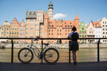Young Woman Traveler With Retro Bicycle  Stand Near River In Old Gdansk City