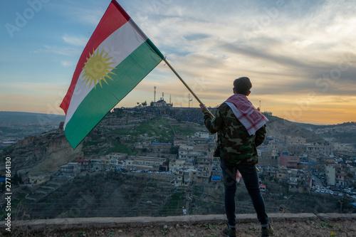 Fotografía  Teenager holding the Kurdistan flag in northern Iraq at sunset time on Nowruz 20