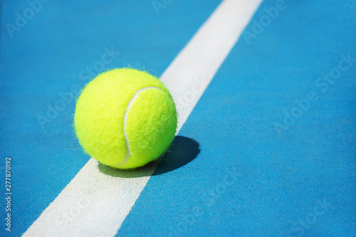 Summer sport concept with tennis ball on white line on hard tennis court. Flat lay, top view, copy space, close up. Blue and green.