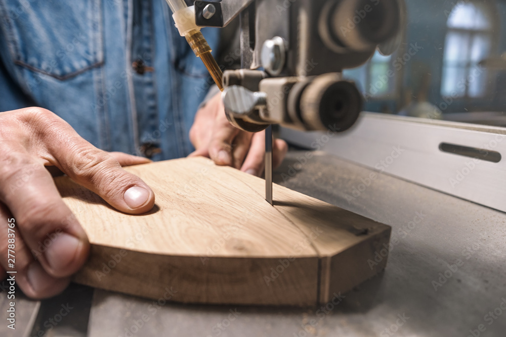 Fototapety, obrazy: young man carpenter builder working with electric jigsaw and wood. Woodworker cutting a piece of wood