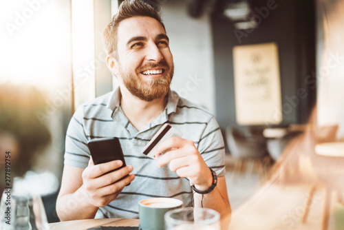 Cuadros en Lienzo  young man shopping online with credit card using smart phone in a cafe