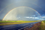 Fototapeta Rainbow - amazingly beautiful view of the rainbow on the horizon of the highway for cars