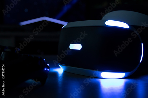 Photo  Brecht, Belgium - June 12 2019: A dark close up of the playstation VR headset with its iconic lights turned on and a playstation 4 controller in front of it