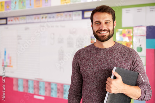 Fotografie, Obraz Portrait Of Male Elementary School Teacher Standing In Classroom