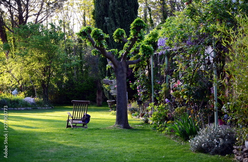 Fototapeta Typical rustic idyllic courtyard garden with wooden armchair obraz