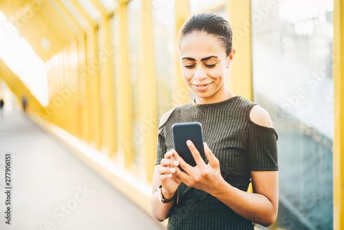 Fotografie, Obraz  An elegant young Brazilian female is using smartphone outdoors.