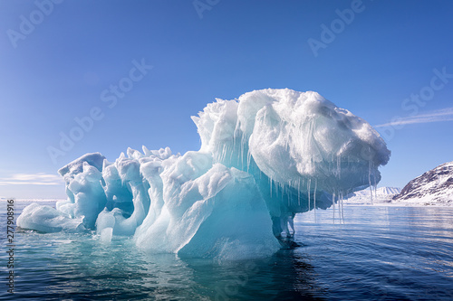 Blue ice iceberg floating in the arctic waters of Svalbard