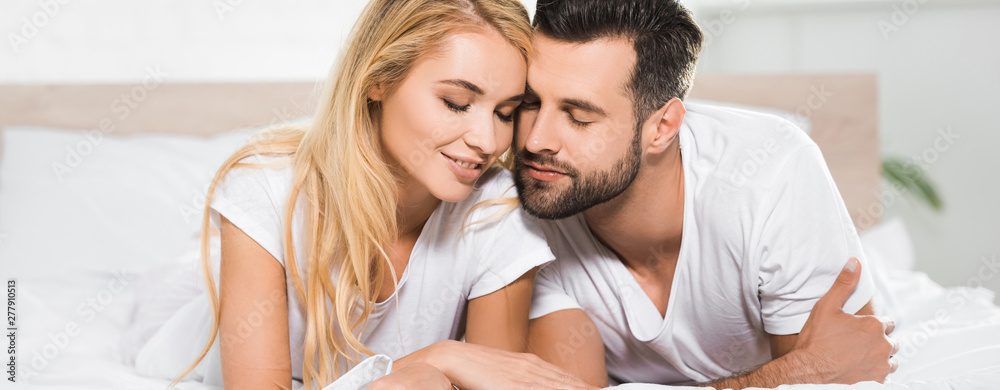 Fototapety, obrazy: panoramic shot of beautiful couple with eyes closed resting on bed at home